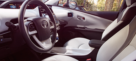 Toyota Prius, interior, light grey leather steering wheel & front seats on display.