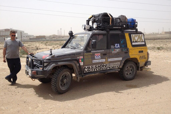 Toyota Land Cruiser, exterior Grey, front side view, man standing in front of vehicle with sunglasses on, in a remote rural area, daytime shot.
