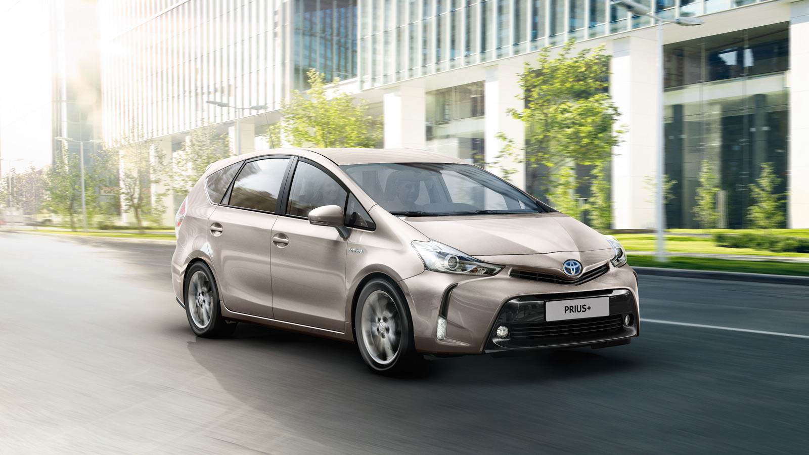 Toyota Prius Plus, exterior Beige, side front view, driving shot in city background