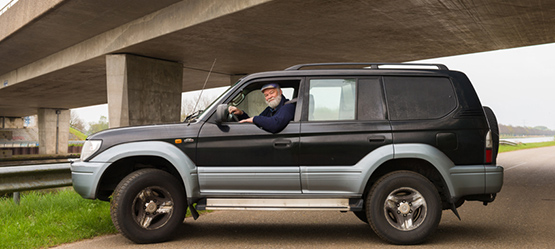 Man in Toyota Land Cruiser onder viaduct